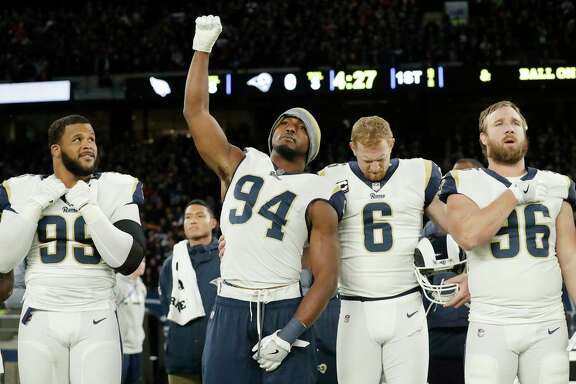Rams outside linebacker Robert Quinn raises his fist during the playing of the national anthem as punter Johnny Hekker (6) bows in observance of the song before Sunday's game against the Cardinals in London.