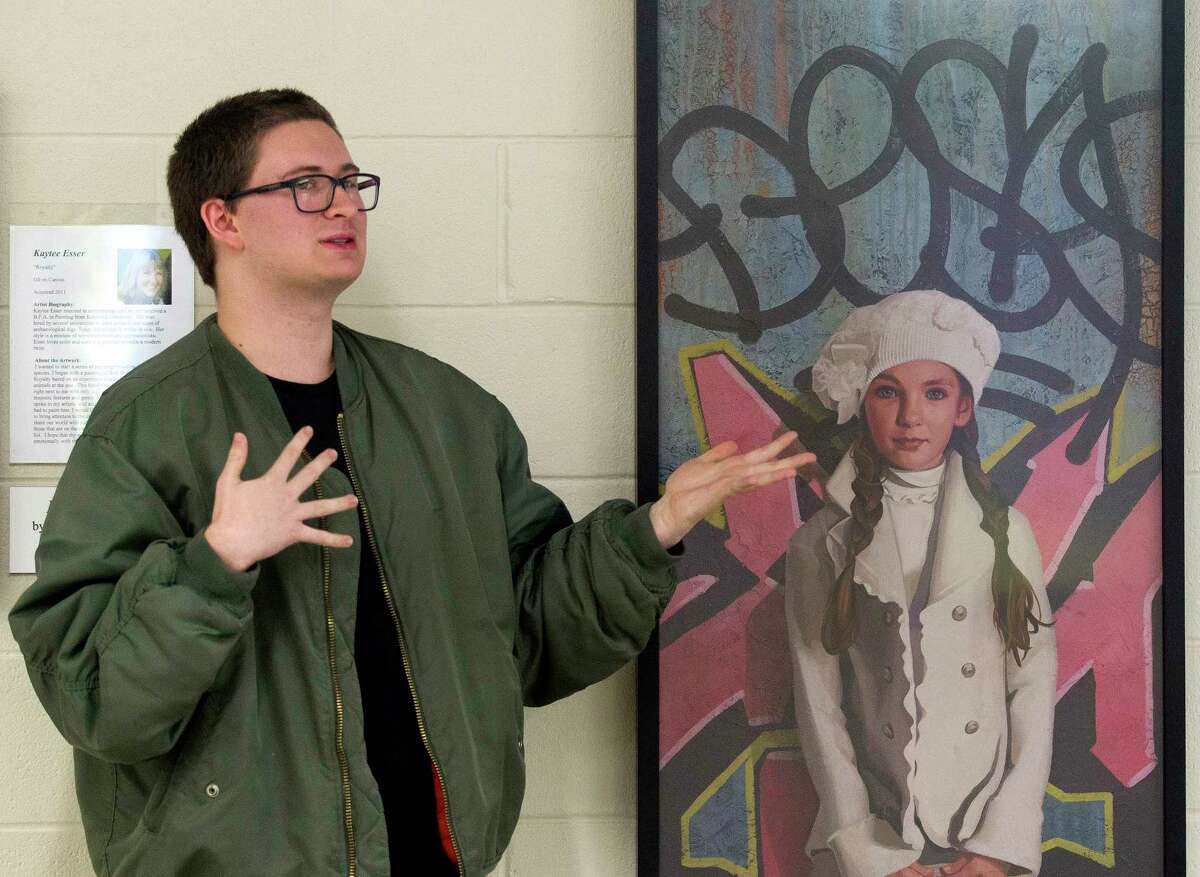 """Ben Herbert, president of the student art trust committee, speaks about his involvement with The Woodlands High School Art Trust beside an work entitled """"White Hat"""" by Kevin Peterson at The Woodlands High School, Wednesday, Oct. 18, 2017, in The Woodlands."""