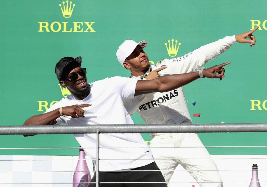 U.S. Grand Prix winner Lewis Hamilton of Great Britain and Mercedes GP celebrates on the podium with sprint legend Usain Bolt. Photo: Mark Thompson, Staff / 2017 Getty Images