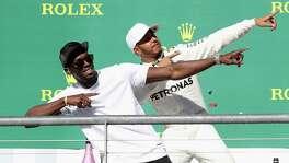 U.S. Grand Prix winner Lewis Hamilton of Great Britain and Mercedes GP celebrates on the podium with sprint legend Usain Bolt.