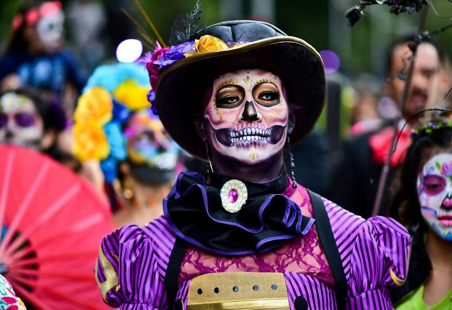"People disguised as ""Catrina"" (Mexican representation of death) take part in the ""Catrinas Parade"" along Reforma Avenue, in Mexico City on October 22, 2017.  Mexicans get ready to celebrate the Day of the Dead highlighting the character of La Catrina which was created by cartoonist Jose Guadalupe Posada, famous for his drawings of typical local, folkloric scenes, socio-political criticism and for his illustrations of ""skeletons"" or skulls, including La Catrina. Photo: RONALDO SCHEMIDT/AFP/Getty Images"