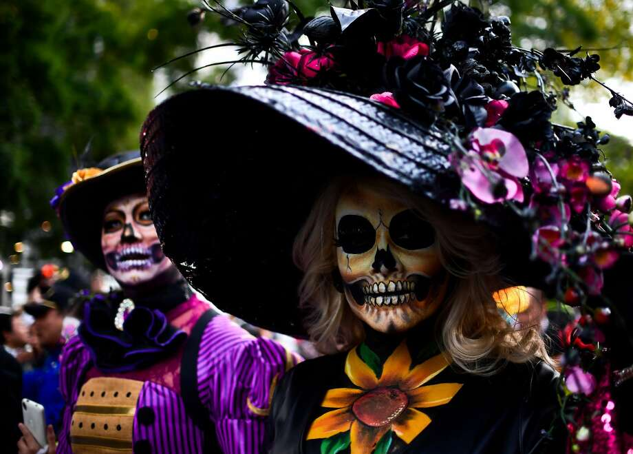 "People fancy dressed as ""Catrina"" take part in the ""Catrinas Parade"" along Reforma Avenue, in Mexico City on October 22, 2017.  Mexicans get ready to celebrate the Day of the Dead highlighting the character of La Catrina which was created by cartoonist Jose Guadalupe Posada, famous for his drawings of typical local, folkloric scenes, socio-political criticism and for his illustrations of ""skeletons"" or skulls, including La Catrina. Photo: RONALDO SCHEMIDT/AFP/Getty Images"