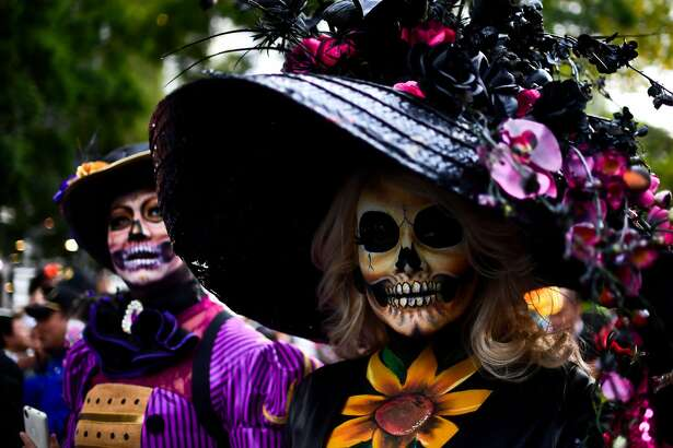 "People fancy dressed as ""Catrina"" take part in the ""Catrinas Parade"" along Reforma Avenue, in Mexico City on October 22, 2017.  Mexicans get ready to celebrate the Day of the Dead highlighting the character of La Catrina which was created by cartoonist Jose Guadalupe Posada, famous for his drawings of typical local, folkloric scenes, socio-political criticism and for his illustrations of ""skeletons"" or skulls, including La Catrina."