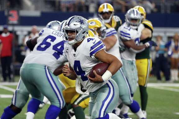 Cowboys quarterback Dak Prescott escapes the pocket to scramble for yards against the Green Bay Packers on Oct. 8 at AT&T Stadium in Arlington.