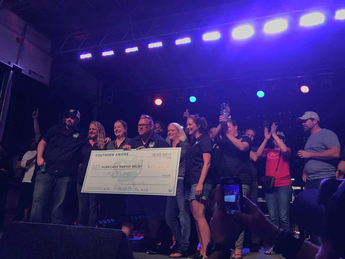Chris Shepherd, center, holds a check for $500,000, which was raised by his Southern Smoke event benefiting hospitality workers affected by Hurricane Harvey.