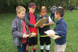 Worden Elementary students Aidan May, Brayden Riney, Scott Phelps and Elijah Huniak work on their science scavenger hunt project recently at Worden Park.