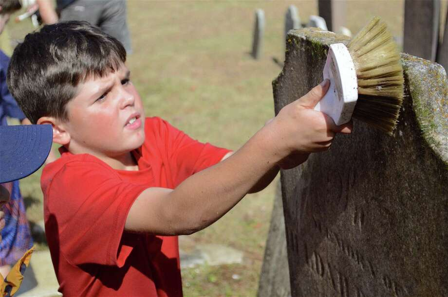 Aedan Messina, 8, of Fairfield, works hard at a restoration project with the scouts of Pack 98 at the Greenfield Hill Cemetery on Bronson Road, Sunday, Oct. 22, 2017, in Fairfield, Conn. Photo: Jarret Liotta / For Hearst Connecticut Media / Fairfield Citizen News Freelance