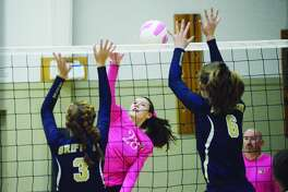 MELHS outside hitter Kate Weber goes up for a kill against two Father McGivney blockers during a regular season match on Oct. 12.