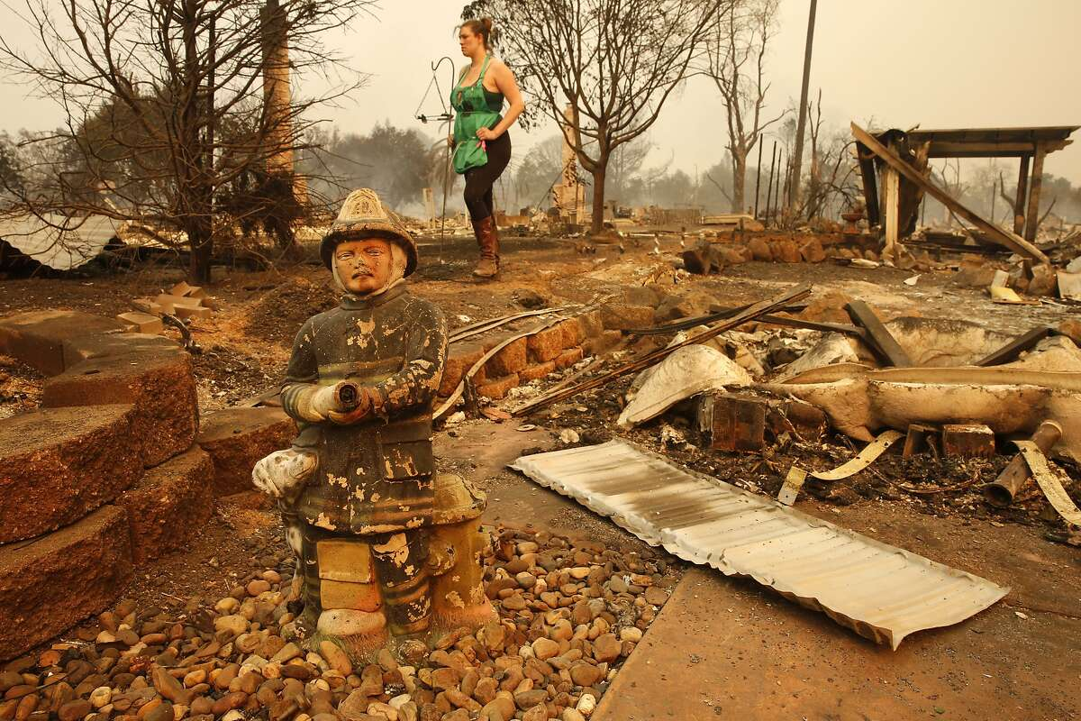 A firefighter figurine remains as Nikki Albrecht looks over her mother's home destroyed in the Tubb's Fire that swept through the Coffey Park neighborhood of Santa Rosa on Oct. 9, 2017.