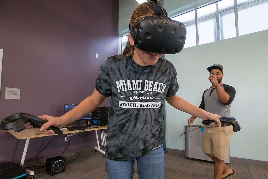 Isabelle Shandersky, 16, reacts as she stands at the edge of a cliff inside a three-dimensional environment using a HMD (head mounted display) and wireless controllers during a virtual reality demonstration given by Jason Flinn (right) at the Universal City Library on Saturday, Oct. 21, 2017. Photo: Marvin Pfeiffer, San Antonio Express-News