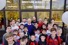 Danbury Mayor Mark Boughton joins Beast Training Wrestling Academy owners Fred Mills and Nicky Weyer, as well as Beast wrestlers at the grand opening of the club's new facility on Eagle Road in Danbury, Conn., on Saturday, Oct. 21, 2017. (Jose Villaluz photo)