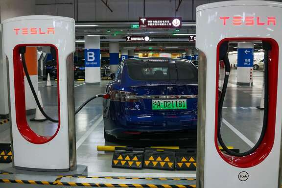A Tesla vehicle is parked at a charging station inside a mall in Shanghai on October 23, 2017.  Tesla has reached an agreement with Shanghai authorities that would make it the first foreign automaker to build its own plant in China, putting it in the driver's seat in the world's biggest electric-vehicle market, the Wall Street Journal reported. / AFP PHOTO / CHANDAN KHANNACHANDAN KHANNA/AFP/Getty Images