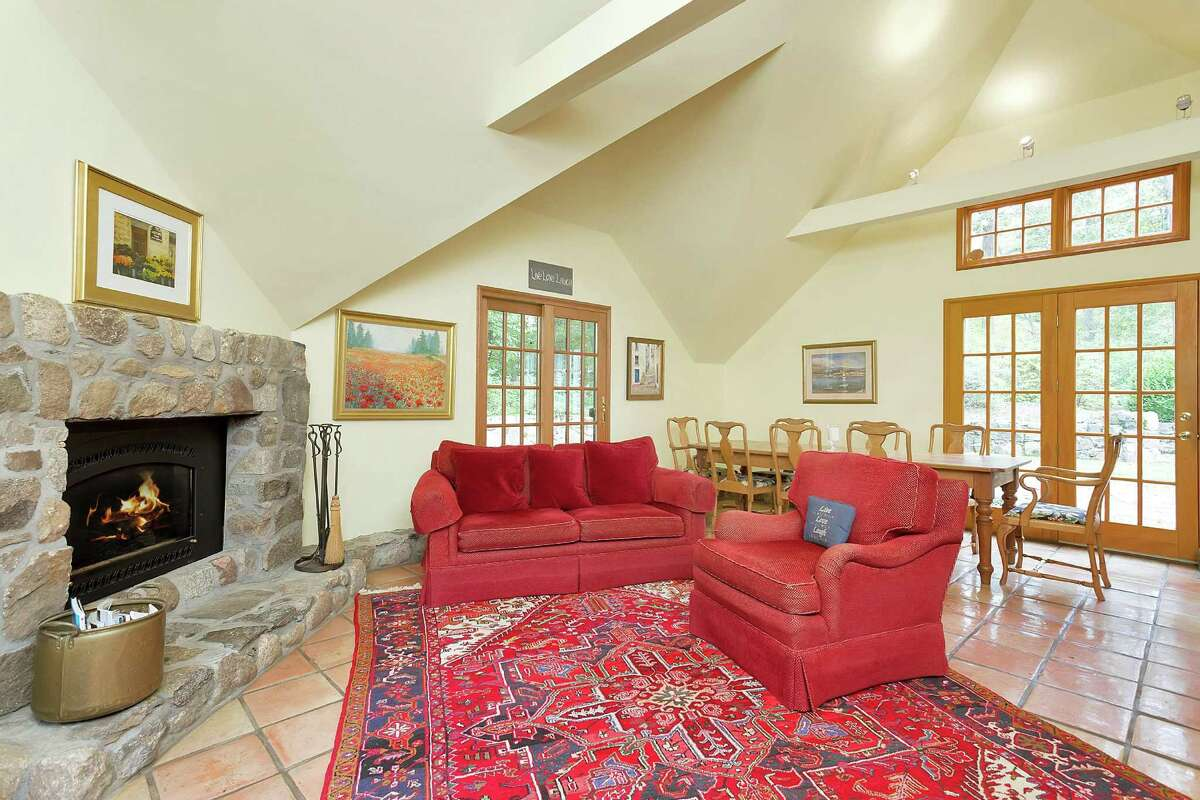 The family room has a stone gas-fueled fireplace, the eat-in section of the kitchen, and three doors on separate walls to the wood deck, courtyard, and side yard.