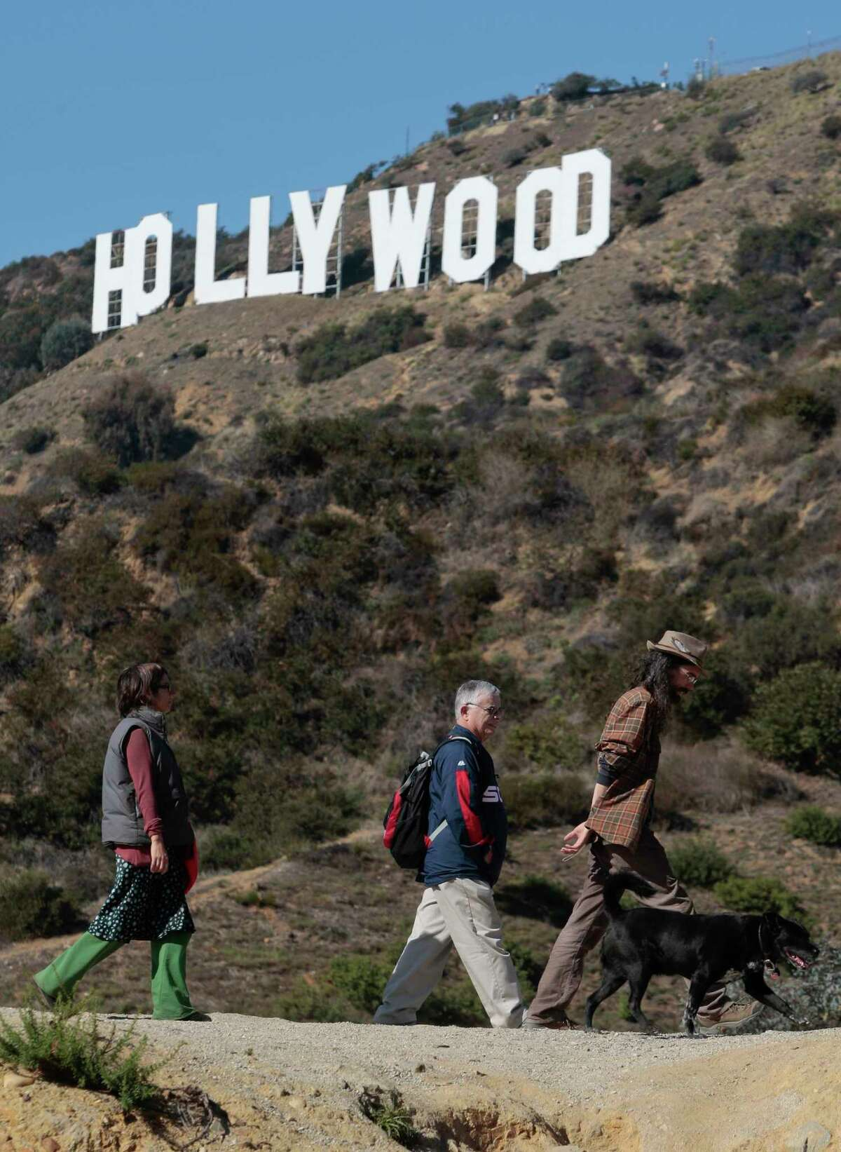A group of hikers walks their dog in Griffith Park near the Hollywood sign after a plastic bag containing a human head was discovered Tuesday by two women walking their dogs on a nearby trail in Los Angeles.