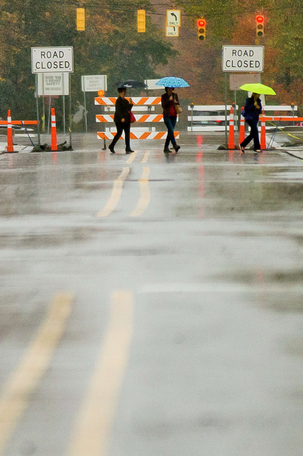 People walk across Main Street carrying umbrellas on Monday, Oct. 23, 2017. The Tittabawassee River is expected to crest at about 1 p.m. Wednesday at 20 feet, 4 feet below flood stage. As of 1:15 p.m. Monday, the river was at 10 feet. (Katy Kildee/kkildee@mdn.net)
