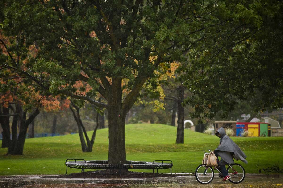 A main rides his bike through steady rain near the Tridge on Monday, Oct. 23, 2017. The Tittabawassee River is expected to crest at about 1 p.m. Wednesday at 20 feet, 4 feet below flood stage. As of 1:15 p.m. Monday, the river was at 10 feet. (Katy Kildee/kkildee@mdn.net)