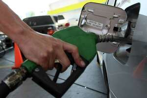 FILE- A person fills up a tank at a gas station. A number of gas stations were reportedly accused of price gouging in the wake of Hurricane Harvey.