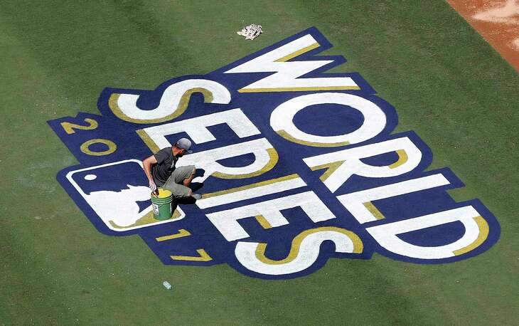Los Angeles Dodgers groundskeepers paint the World Series logo on the field during the World Series Media Day at Dodger Stadium, Monday, Oct. 23, 2017, in Los Angeles.