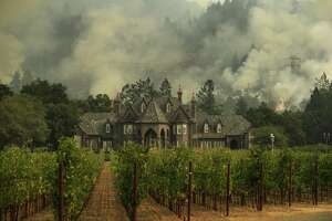 A wildfire burns behind a winery Saturday, Oct. 14, 2017, in Santa Rosa, Calif.