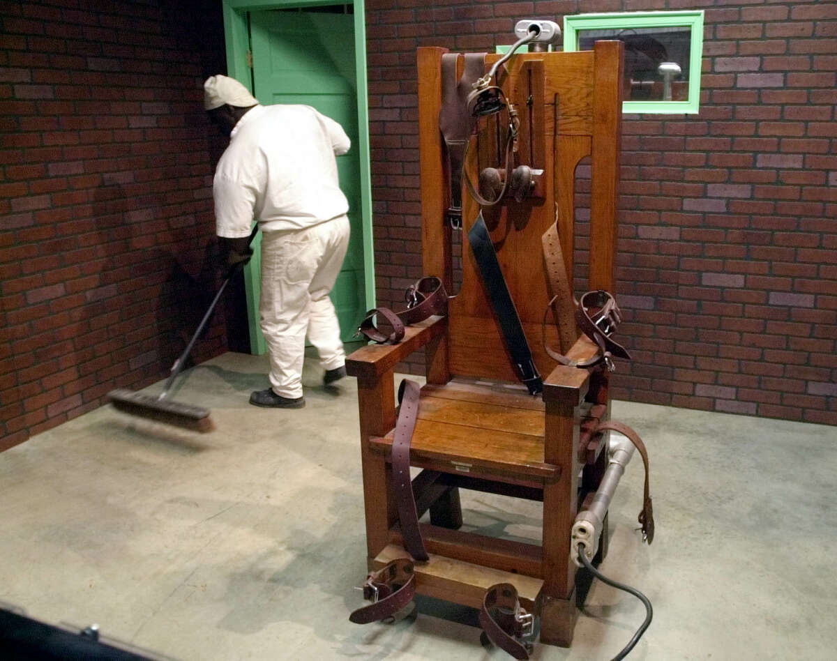 """A prison inmate sweeps the floor around """"Old Sparky,"""" the famous old Texas electric chair, in the Texas Prison Museum in Huntsville. (Associated Press)"""