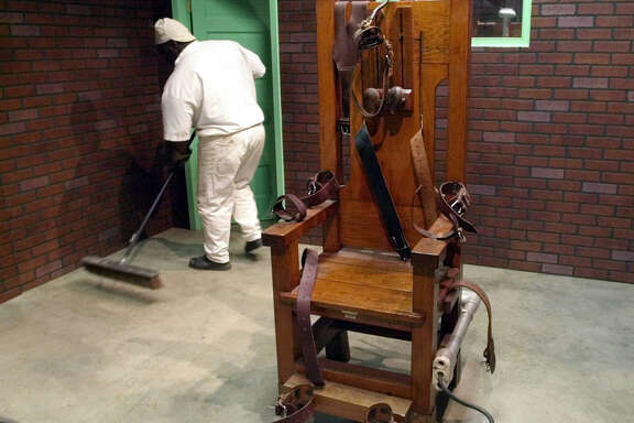 "A prison inmate sweeps the floor around ""Old Sparky,"" the famous old Texas electric chair, in the Texas Prison Museum in Huntsville. (Associated Press)"