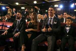 El portugués Cristiano Ronaldo, segundo de derecha a izquierda, y su hijo Cristiano Ronaldo Jr., derecha, presencian el evento sentados al lado del astro argentino Lionel Messi, izquierda, y su esposa Antonella durante la entrega de premios The Best de FIFA 2017, en el Palladium Theatre de Londres, el lunes 23 de octubre de 2017. (AP Foto/Alastair Grant)