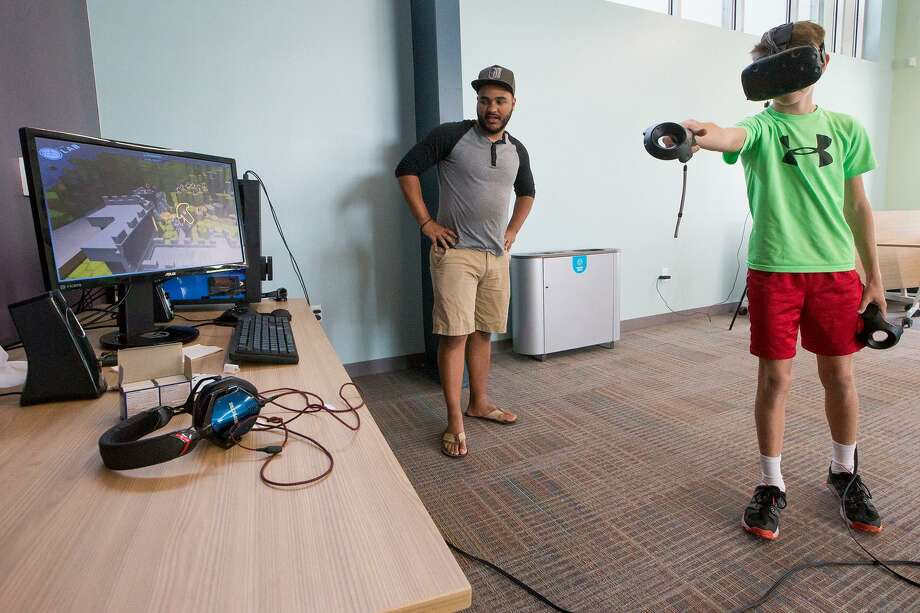 Nathaniel Shandersky (right), 12, uses wireless controllers and a HMB (head mounted display) to navigate inside a three-dimensional environment as Jason Flinn gives a virtual reality demonstration at the Universal City Library on Saturday, Oct. 21. Photo: Marvin Pfeiffer /San Antonio Express-News / Express-News 2017