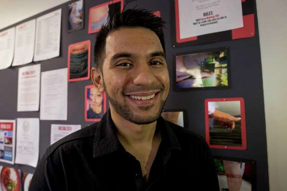 Medology CEO Fiyyaz Pirani in front of a board with photographs of employees who have gotten Medology tattoos Wednesday, Oct. 11, 2017, in Houston. ( Godofredo A. Vasquez / Houston Chronicle )