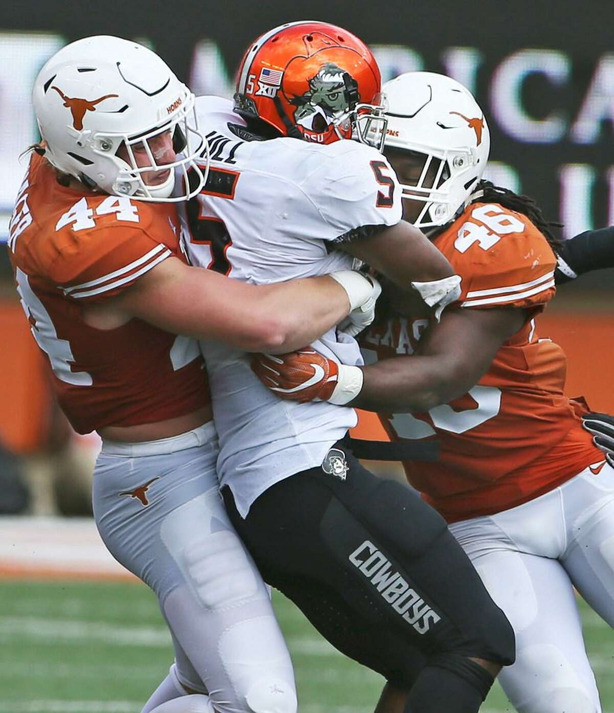 Texas linebackers Breckyn Hager and Malik Jefferson tackle Oklahoma State's Justice Hill during OSU's overtime victory Oct. 21, 2017 in Austin.