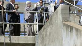 SAWS CEO Robert Puente (right) joins in a drink of clean water emerging from the plant as Environmental Protection Agency Administrator Gina McCarthy visits the Dos Rios Water and Recycling Center and Centennial Solar Farms with Mayor Julian Castro in 2014. Rate hikes are necessary because the EPA and SAWS have agreed to a $500 million in infrastructure improvments that the city failed to do earlier.
