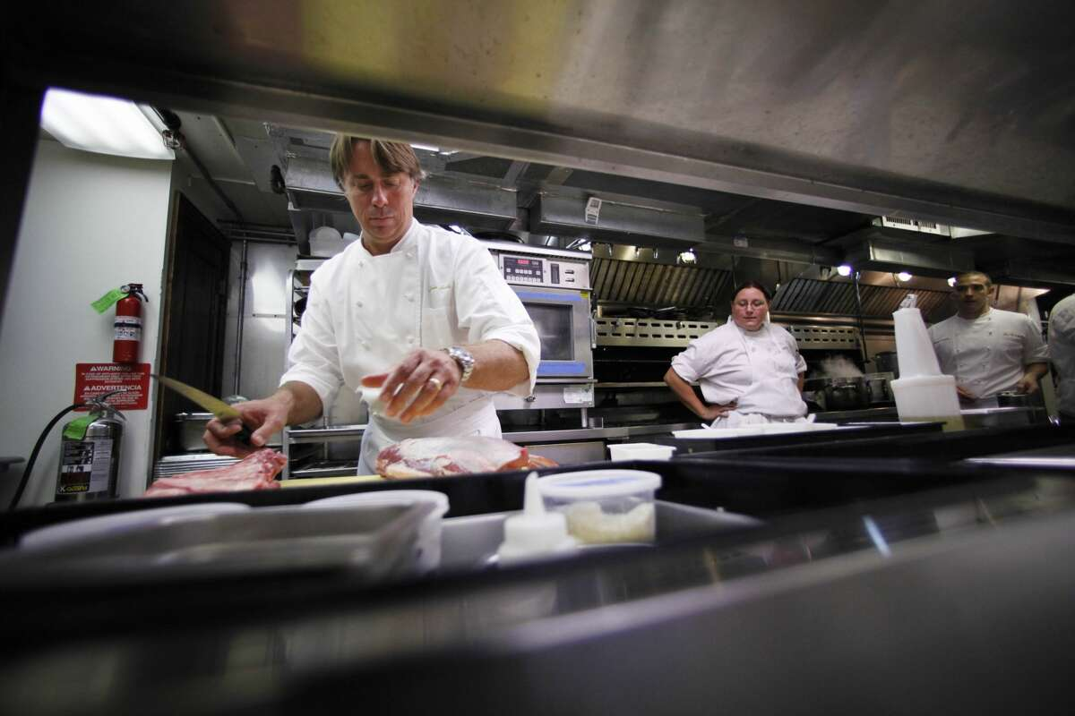 In this Monday, Sept. 27, 2010 picture, Chef John Besh prepares food in the kitchen of his restaurant 'August' in New Orleans. Besh's two restaurants were spared when Hurricane Katrina barreled through New Orleans five years ago, but the storm almost wiped him out anyway, sending his customers looking for dry ground. At the suggestion of an old Marine Corps buddy, Besh decided to cook the food and serve it to stranded residents and first responders brought to the city by the hurricane. (AP Photo/Gerald Herbert)