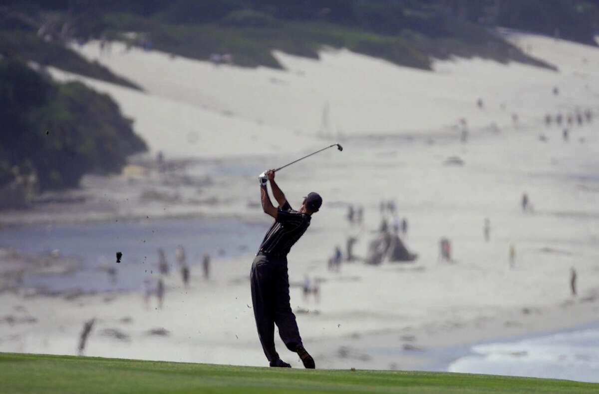 Tiger Woods, of Windermere, Fla., tees off on the ninth hole with Carmel Beach as a backdrop during the first round of the 100th U.S. Open Golf Championship at the Pebble Beach Golf Links in Pebble Beach, Calif., Thursday, June 15, 2000. (AP Photo/Lenny Ignelzi)