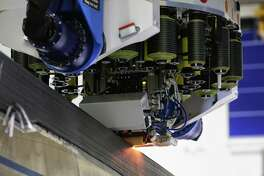 Automated machinery lays down carbon fiber composite to build wings for the 777x in their new Composite Wing Facility during a kick off event for production on the new 777x, Monday, Oct. 23, 2017 in Everett.