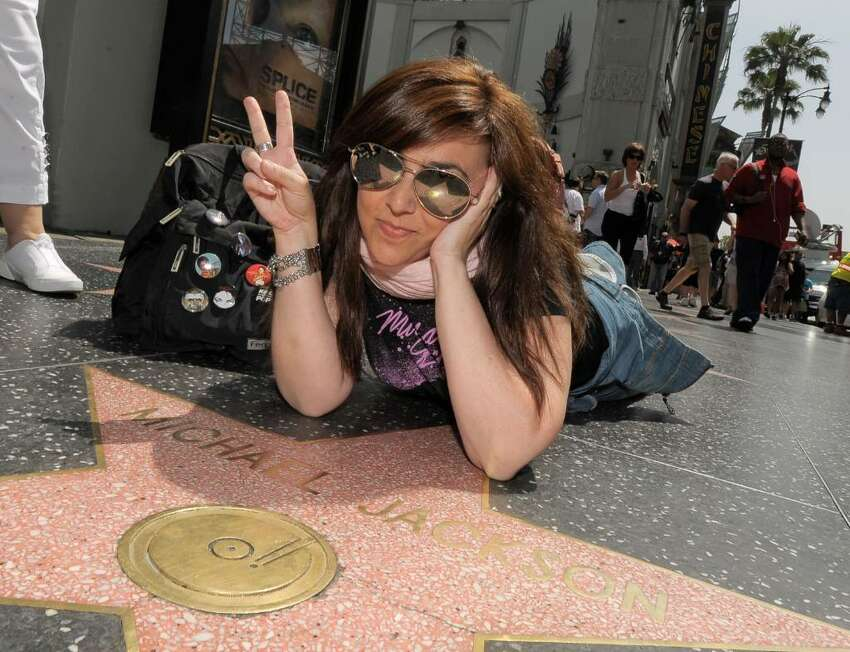 LOS ANGELES, CA - JUNE 24: Fans of the late pop star Michael Jackson pose with his star on the Hollywood Walk of Fame to commemorate the first anniversary of his death on June 24, 2010 in Los Angeles, California. (Photo by Charley Gallay/Getty Images)