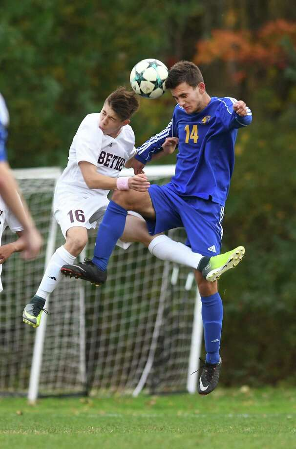 Bethel's Maykel Mariano (19), left, and Newtown's Thomas Skhreli (14) right, compete for a header during the boys soccer game between Newtown and Bethel high schools at Bethel, October 23, 2017. Photo: Krista Benson / The News-Times Freelance