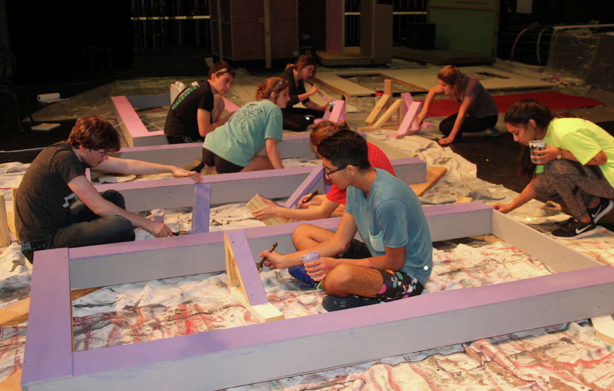 Tech crew members work on some of the 21 double-sided units that will create the sets for The John Cooper SchoolÂ?'s production of Â?