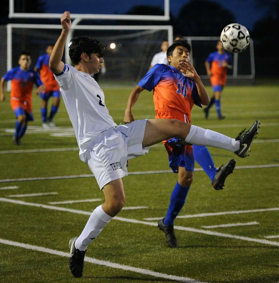 Trumbull's Nicholaos Xenakis, left, converges on the ball with Danbury's Chriss Sari during their boys soccer game at Trumbull High School in Trumbull, Conn. on Monday, October 23, 2017. Photo: Brian A. Pounds / Hearst Connecticut Media / Connecticut Post