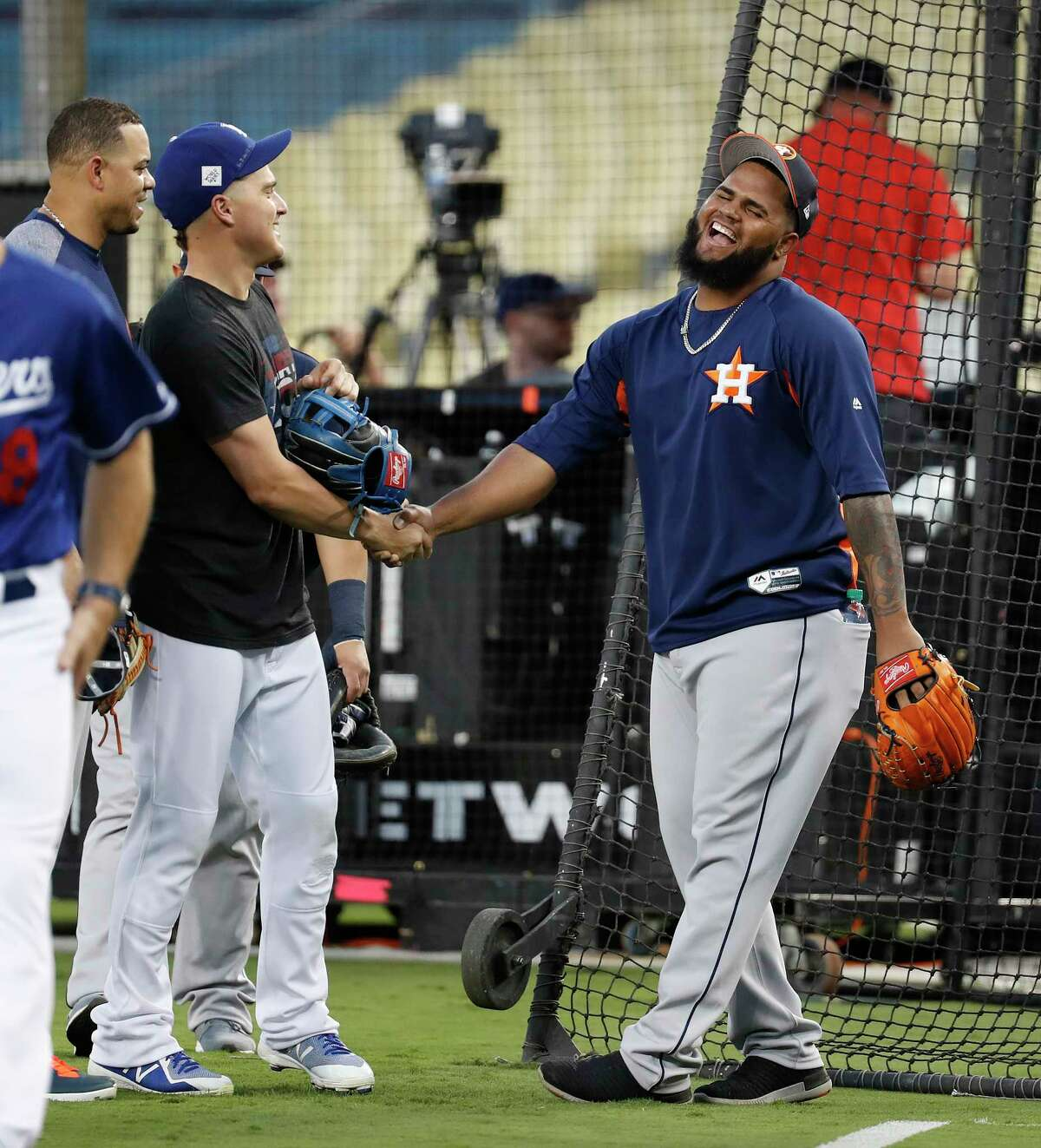 Los Angeles Dodgers center fielder Kike Hernandez laughs with Houston Astros Francis Martes as the Dodgers worked out during the World Series Media Day at Dodger Stadium, Monday, Oct. 23, 2017, in Los Angeles.