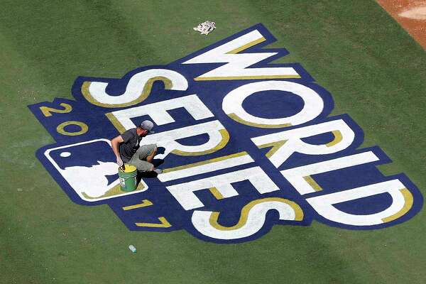 Los Angeles Dodgers groundskeepers paint the World Series logo on the field during the World Series Media Day at Dodger Stadium, Monday, Oct. 23, 2017, in Los Angeles. ( Karen Warren / Houston Chronicle )