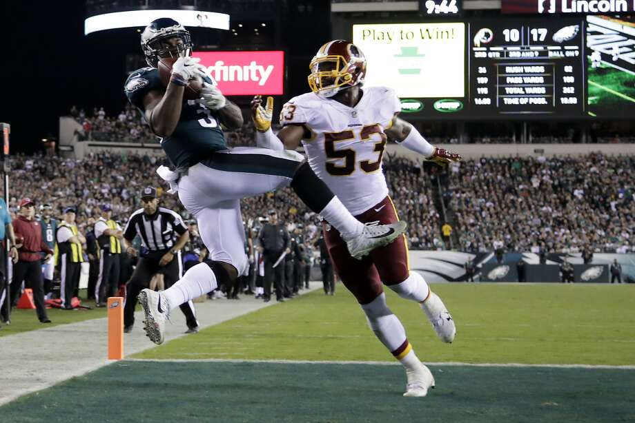 Corey Clement catches one of Carson Wentz's four scoring passes behind Washington's Zach Brown. Photo: Michael Perez, Associated Press