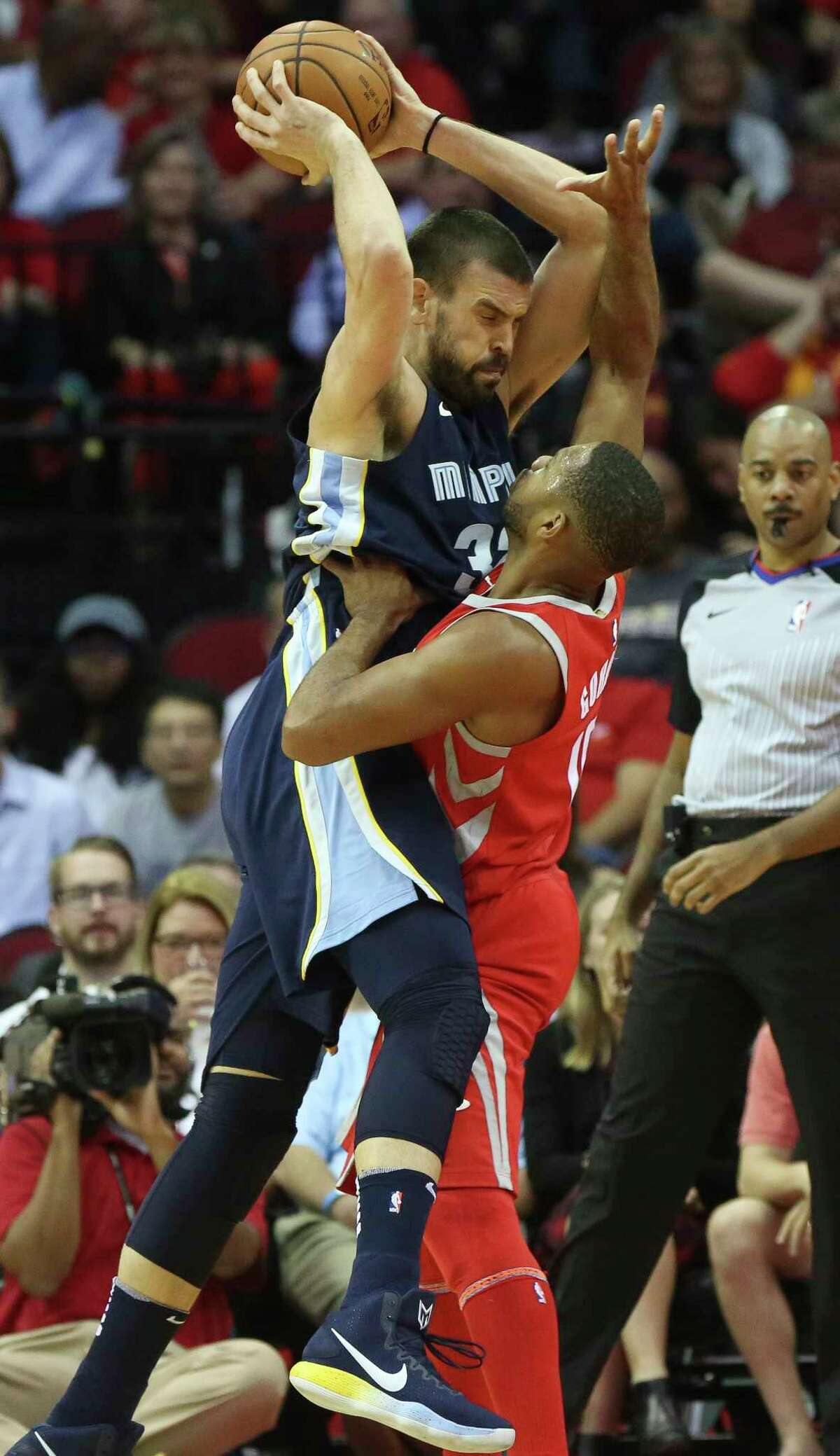 Rockets guard Eric Gordon, right, sacrifices his body to try to stop 7-1 Grizzlies center Marc Gasol in the paint during the second quarter Monday night.