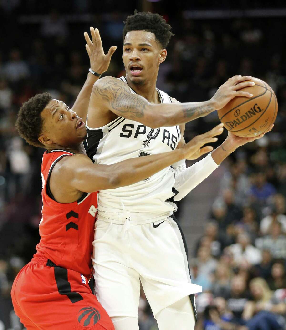 San Antonio Spurs?• Dejounte Murray looks to pass around Toronto Raptors?• Kyle Lowry during first half action Monday Oct. 23, 2017 at the AT&T Center.
