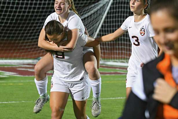 Mohonasen's Lexi Canavalley carries Alex Skoda off the field after she assisted Skoda to score the winning goal in a multiple overtime semi-final soccer game against Averill Park on Monday, Oct 23, 2017 in Stillwater, N.Y. Isabella O'Clair, #3, walks with them. (Lori Van Buren / Times Union)