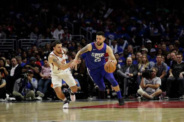 Los Angeles Clippers' Austin Rivers drives past Phoenix Suns' Mike James during the second half of an NBA basketball game Sunday, Oct. 22, 2017, in Los Angeles. (AP Photo/Jae C. Hong)