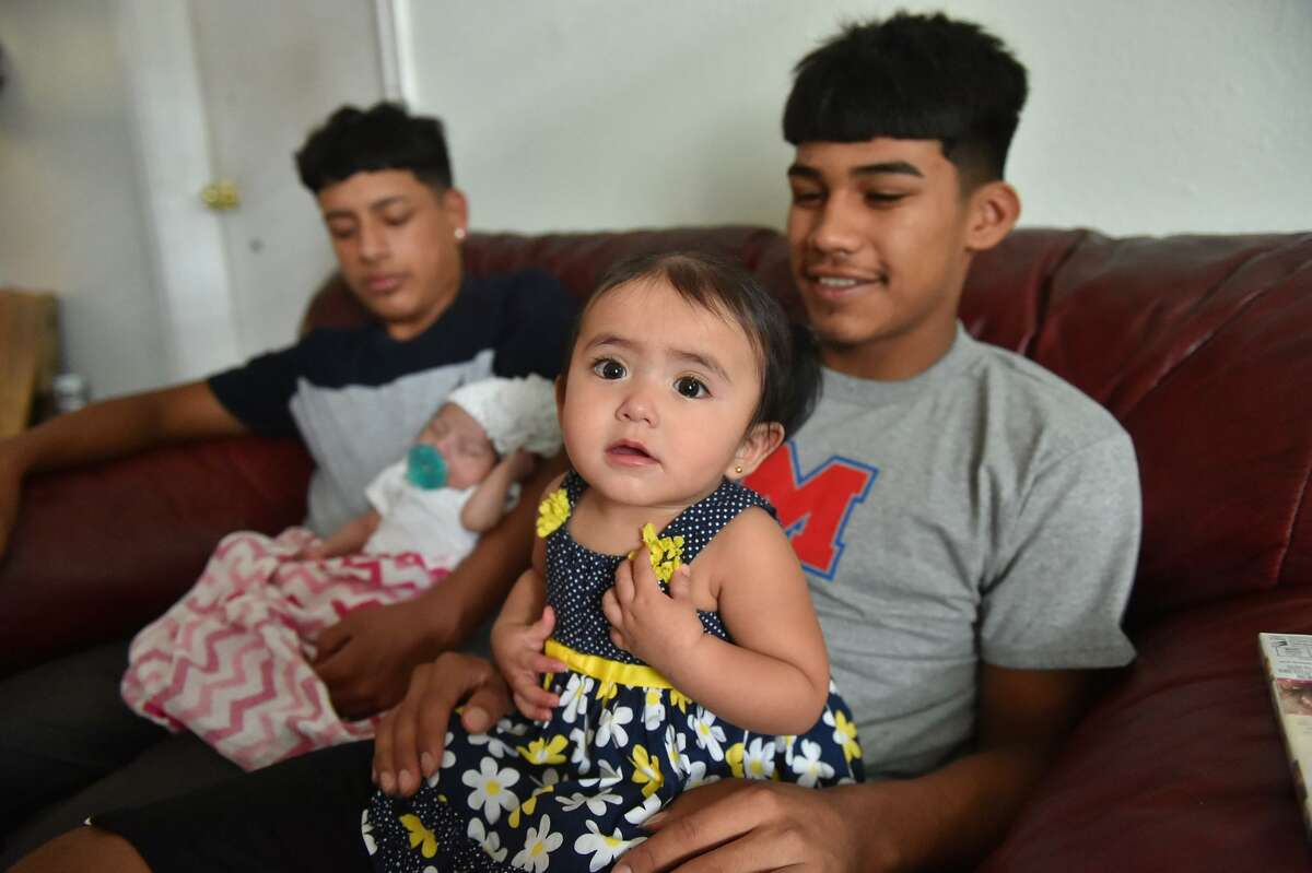 Averee Urdiales, 10 months, sits on the lap of her father, Memorial High School football player Carlos Urdiales as his teammate Lee Guerrero sits with his 1-month-old daughter, Maylanie.