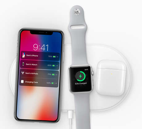 An iPhone X, Apple Watch and AirPods case are charging on Apple's upcoming AirPower charging mat.