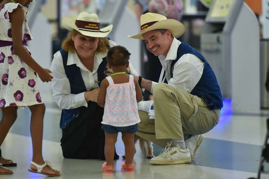 Airport Ambassadors Claudia and Jason Fisch of the Pups and Planes program at the San Antonio International Airport smile and laugh with 1 year old Kennedy Haire recently. Photo: Robin Jerstad, Freelance / San Antonio Express News / ROBERT JERSTAD