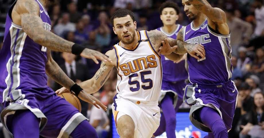Phoenix Suns guard Mike James (55) drives as Sacramento Kings center Willie Cauley-Stein, left and Sacramento Kings guard George Hill, right, during the second half of an NBA basketball game, Monday, Oct. 23, 2017, in Phoenix. The Suns won 117-115. (AP Photo/Matt York)