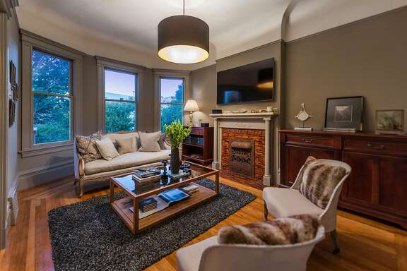 The sitting room houses a fireplace and dual-hung picture windows.