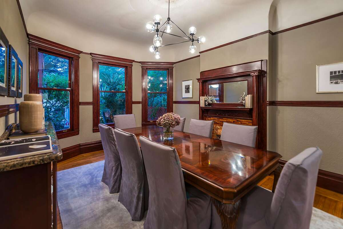 The formal dining room boasts contemporary lighting, a coved ceiling, and a fireplace.